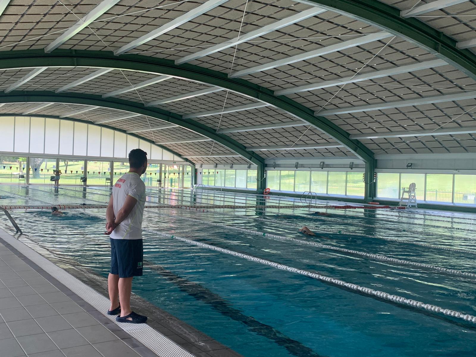 Un socorrista vigila el nado de unos abonados en la piscina cubierta.